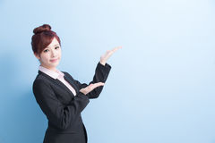Business woman show something. Business woman is smile and show something to you with  on blue background, asian Stock Photography