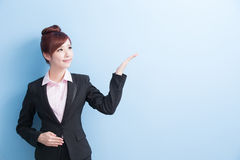 Business woman show something. Business woman is smile and show something to you with isolated on blue background, asian Royalty Free Stock Images
