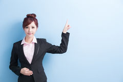 Business woman show something. Business woman is smile and show something to you with isolated on blue background, asian Stock Photo
