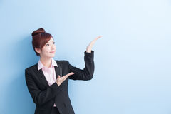 Business woman show something. Business woman is smile and show something to you with isolated on blue background, asian royalty free stock photography