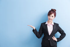 Business woman show something. Business woman is smile and show something to you with isolated on blue background, asian Stock Image