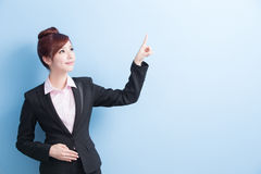 Business woman show something. Business woman is smile and show something to you with isolated on blue background, asian royalty free stock photos