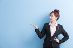 Business woman show something. Business woman is smile and show something to you with isolated on blue background, asian stock photography