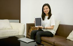 Business woman showing a blank screen tablet in living room at n royalty free stock images