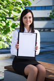 Business woman showing clipboard with copy space in city park Royalty Free Stock Photo