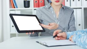 Business woman showing digital tablet to coworkers in office. Stock Image