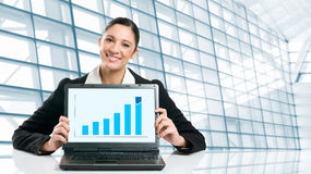 Business woman showing growing chart. Young business woman displaying successful growing graph on her laptop in a modern office Stock Photos