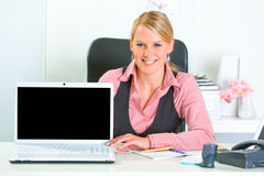Business woman showing laptop with blank screen Stock Photo