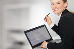 Business woman showing laptop screen and pen. Grey background Royalty Free Stock Image