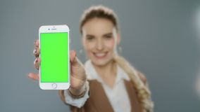 Business woman showing mobile phone with green screen in studio