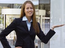 Business Woman - Showing a product in her hand. A female business person is showing off a product in her hand stock photos