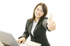 Business woman showing thumbs up sign. Asian business woman sitting at desk working on laptop Stock Images