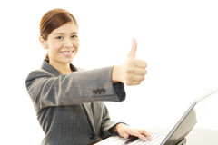 Business woman showing thumbs up sign. Asian business woman sitting at desk working on laptop Royalty Free Stock Photos