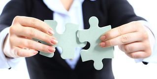 Business woman showing two jigsaw puzzle pieces Royalty Free Stock Photography