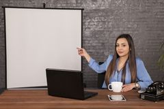 Business woman shows a finger at an empty whiteboard royalty free stock images