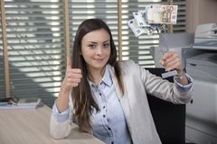 Business woman shows a statuette of money, success in business,. Thumb up, woman in the office situation royalty free stock photo