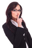 Business woman shuts you up. Young business woman making the shut up gesture with her finger at her mouth. on white background stock photography
