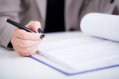 Business woman signing a contract above signature line. Close up girl hand putting signature on document. She situating at desk. Business concept. Low angle Royalty Free Stock Photo