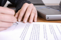 Business woman signing a contract in office. Hands signing a contract with laptop in background Stock Image