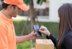 Business woman signing on mobile device receiving package delivery. Business women is signing on mobile device receiving package delivery Royalty Free Stock Images