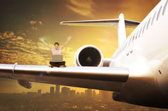 Business woman sit on airplane wing working with laptop Royalty Free Stock Images
