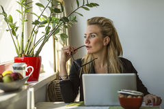 Business woman sits pensively beside a window with a laptop. Royalty Free Stock Photography