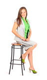 Business woman sits on stool in studio Stock Images