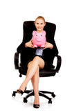 Business woman sitting on armchair and holding piggybank Stock Image