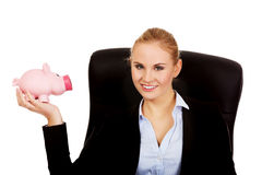 Business woman sitting on armchair and holding piggybank Royalty Free Stock Photo