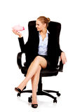Business woman sitting on armchair and holding piggybank Royalty Free Stock Image