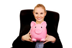 Business woman sitting on armchair and holding piggybank Royalty Free Stock Photography