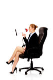 Business woman sitting on armchair and screaming through a megaphone Royalty Free Stock Photos