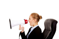 Business woman sitting on armchair and screaming through a megaphone Royalty Free Stock Photography