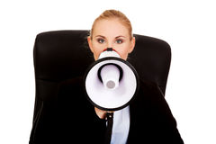 Business woman sitting on armchair and screaming through a megaphone Royalty Free Stock Photo
