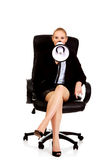 Business woman sitting on armchair and screaming through a megaphone Stock Photos