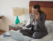 Business woman sitting on bed in room and working Royalty Free Stock Image