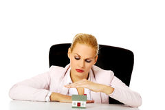 Business woman sitting behind the desk with house model Stock Photos