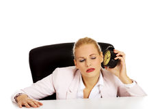 Business woman sitting behind the desk and listen to alarm clock Royalty Free Stock Image