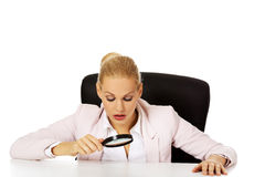 Business woman sitting behind the desk and looking into a magnifying glass Royalty Free Stock Images