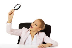 Business woman sitting behind the desk and looking into a magnifying glass Royalty Free Stock Image