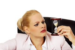 Business woman sitting behind the desk and looking for sandglass Royalty Free Stock Photos