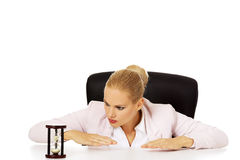 Business woman sitting behind the desk and looking for sandglass Royalty Free Stock Photography