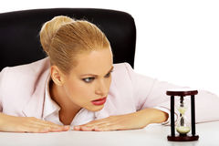Business woman sitting behind the desk and looking for sandglass Royalty Free Stock Photo
