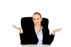 Business woman sitting behind the desk and making don't know sing Royalty Free Stock Photo