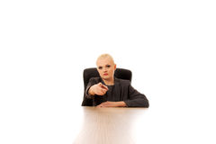 Business woman sitting behind the desk and pointing at camera Royalty Free Stock Image