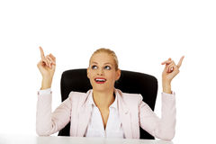 Business woman sitting behind the desk and pointing up for copyspace or something Stock Photography