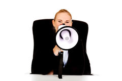 Business woman sitting behind the desk and screaming through a megaphone Royalty Free Stock Photos