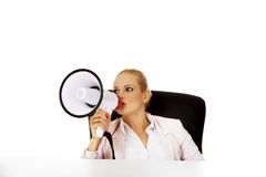 Business woman sitting behind the desk and screaming through a megaphone Royalty Free Stock Images