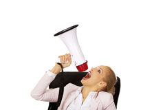 Business woman sitting behind the desk and screaming through a megaphone Stock Photography