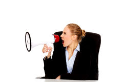 Business woman sitting behind the desk and screaming through a megaphone Stock Images
